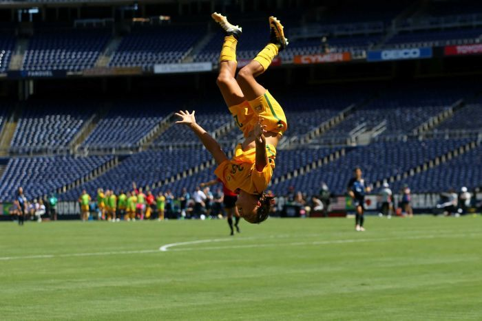 Australian footballer Sam Kerr is upside-down, in mid-back flip.