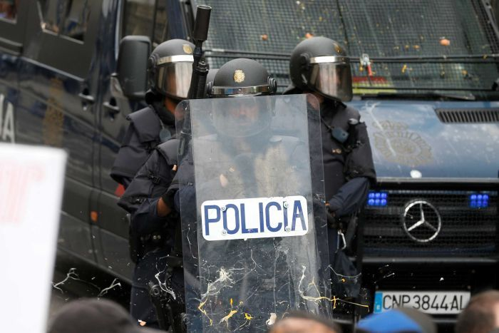 Spanish police in helmets hold a shield.