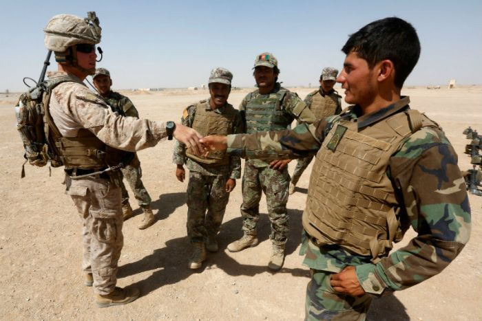 US Marine shakes hand with Afghan National Army soldiers in the desert