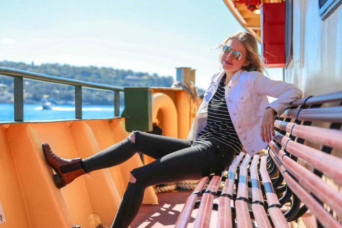 Amy Lyons sits on a bench on a Sydney Harbour ferry