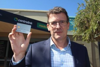 Human Services Minister Alan Tudge holding a cashless welfare card while standing outside Centrelink in Kalgoorlie.