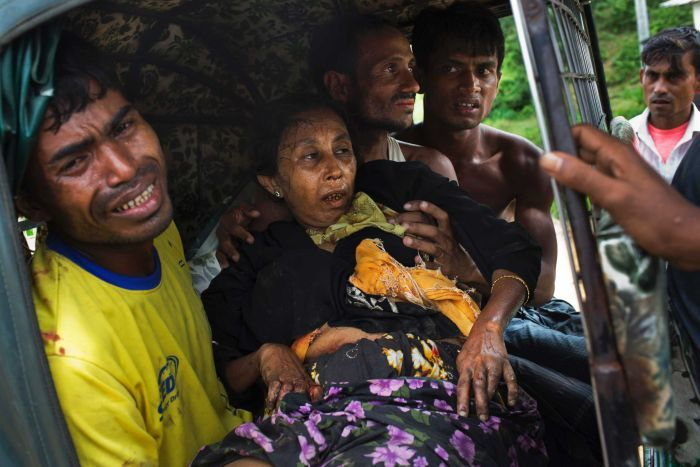 An injured elderly woman, who appears to be in great pain, held by her male relatives on an autorickshaw.