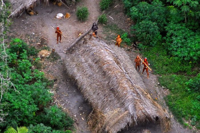 Five indigenous tribe members stand near a hut with spears in the Amazon