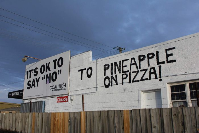 Wiseguise pizza shop workers alter an anti-SSM billboard in Launceston.