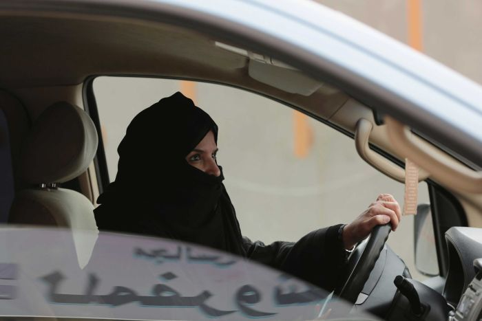 A Saudi woman wearing a head covering driving a car.