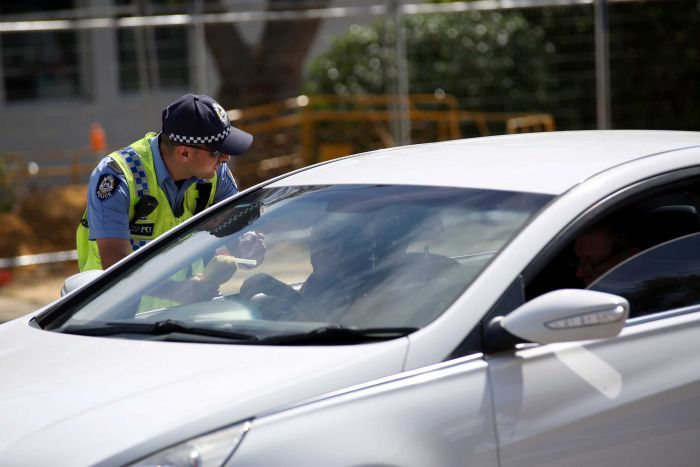 A policeman leans into the window of a car holding a breathalyser.