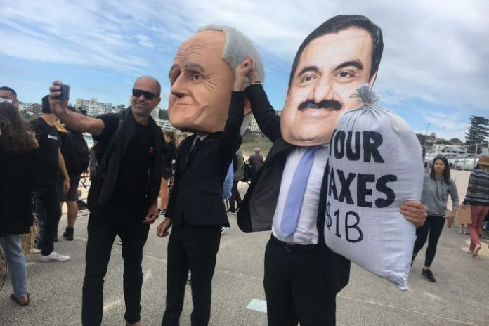 A man takes a selfie with a fake Malcolm Turnbull and Guatam Adani.