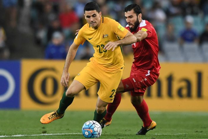 Australia's Tom Rogic runs with the ball as Syria's Tamer Mohamad challenges during the 2018 World Cup qualifying football match