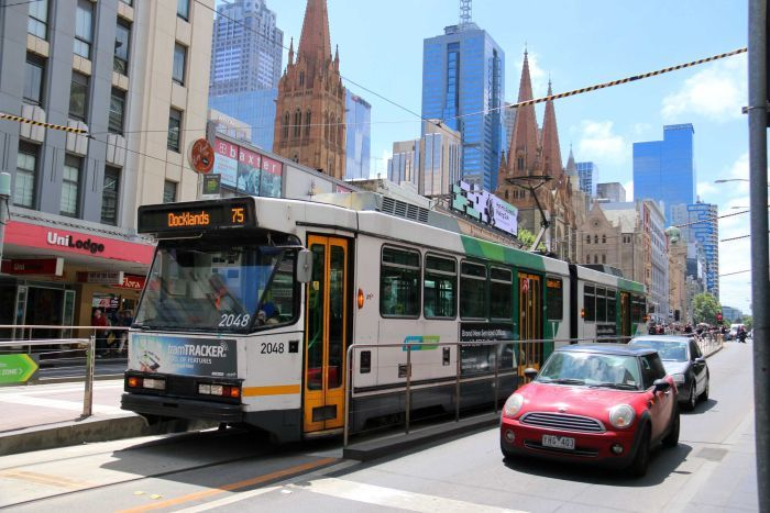 A number 75 tram travels along Flinders Street in Melbourne's CBD