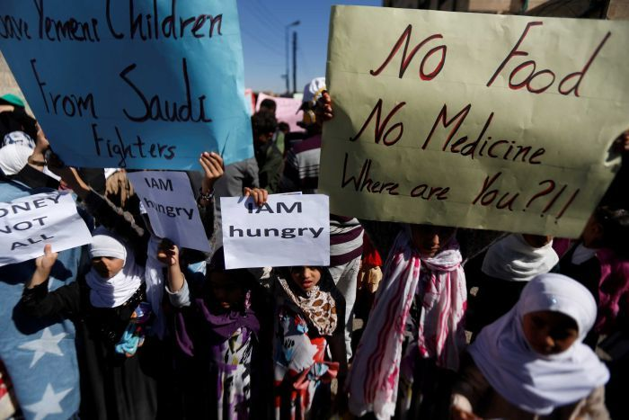 """Children holding large signs saying 'No food, no medicine, where are you?!!"""""""