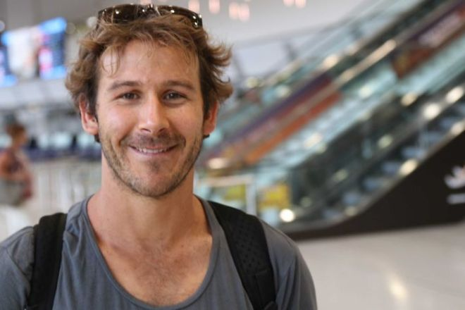 A smiling Josh Clift looks into the camera, with an out of focus stairway and escalators behind him.
