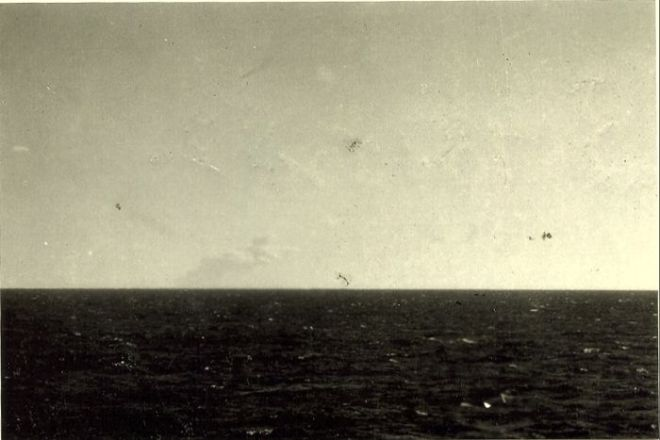 In an old photograph, a plume of smoke is only just visible on the ocean horizon
