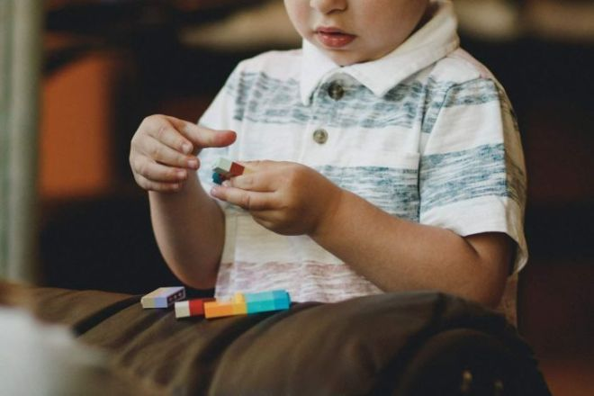 A child plays with blocks on a sofa.