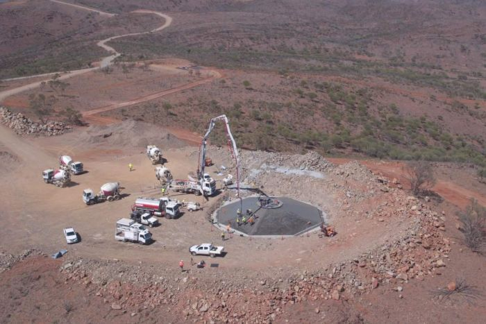 An aerial shot of trucks and cranes surrounding a concrete base which is in the process of being poured.
