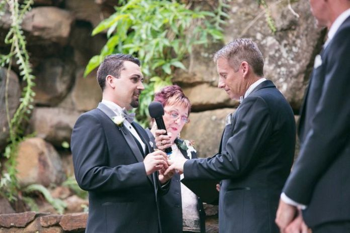 Two men exchanging rings in a civil ceremony.