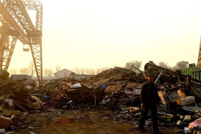 A worker at a scrap metal recycling facility at Tongzhou, Beijing.