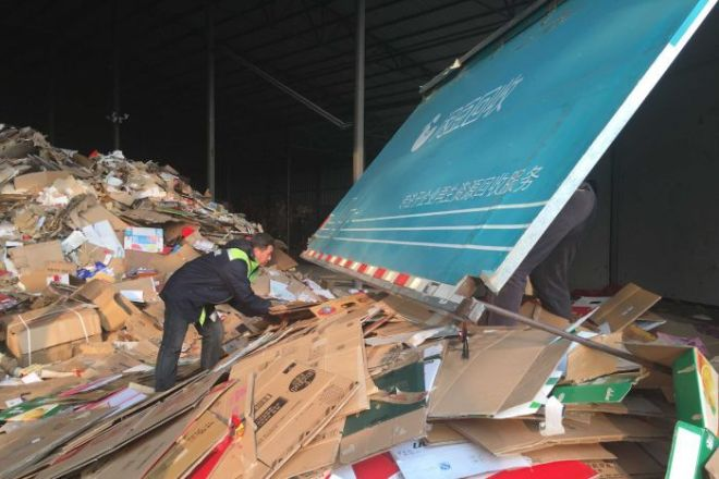 Cardboard collection workers sort boxes at a recycling facility in Beijing.