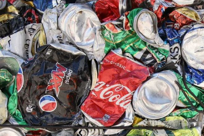 Pepsi, Coke, and alcoholic drink cans are crushed and cubed and stacked next to each other.