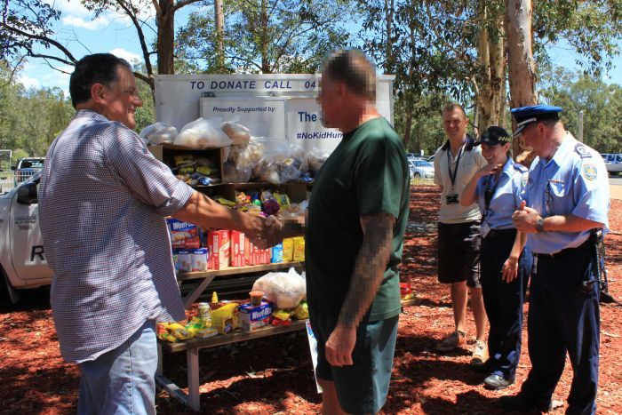 Blurred image of prisoner shaking hands with charity owner when handing over food donation.