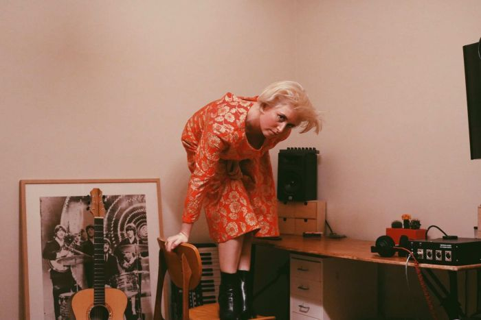 Sydney electronic artist Phebe Starr stands on a chair in front of a guitar and other musical equipment