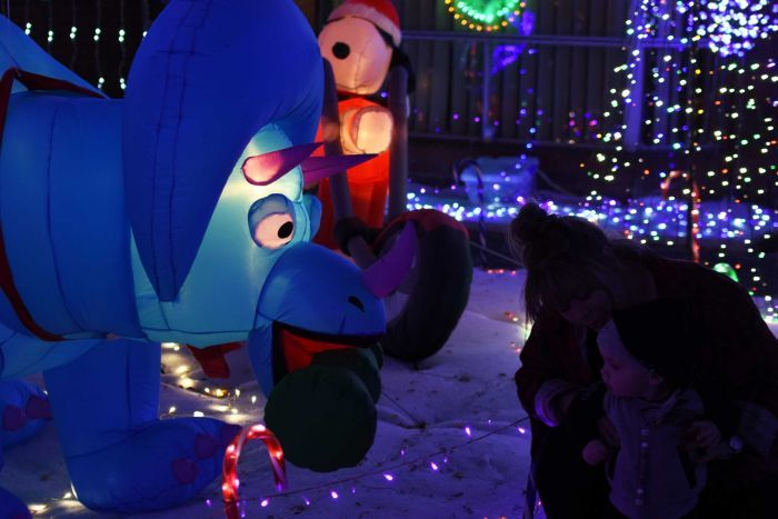 An inflatable dinosaur is surrounded by Christmas lights.