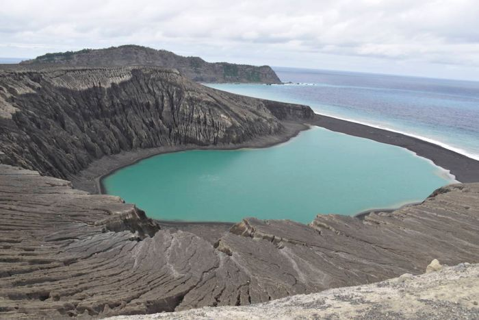 A wide shot shows the cliffs and black sand of a small island.