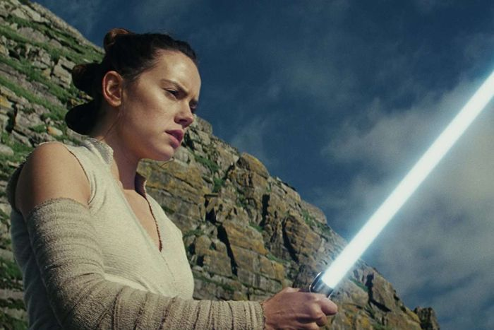 Rey holds a lightsaber, while standing in front of a cliff.