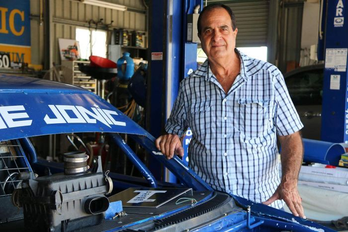 Flood victim Lubo Jonic stands beside his son's race car in his warehouse at Goodna.