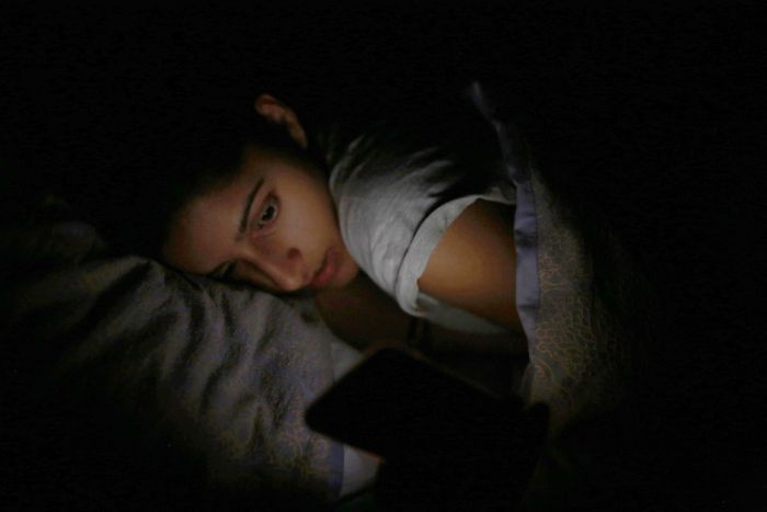 Somya looks at her phone as she lies in bed.