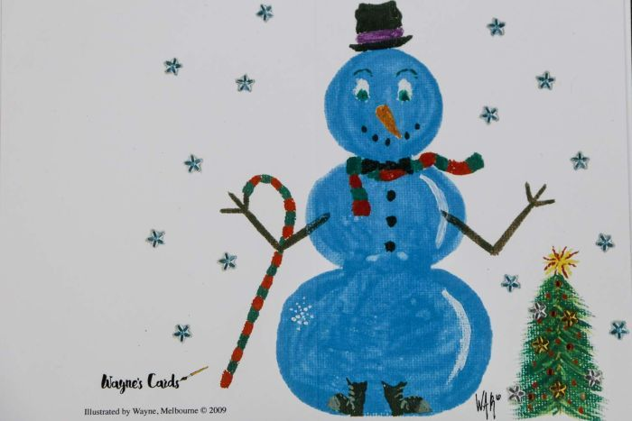 A Christmas card with a large blue snowman next to a green Christmas tree.