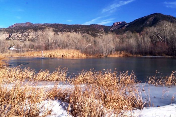 Landscape picture of a frozen pond surrounded by mountains and dry shrubbery on a sunny day.