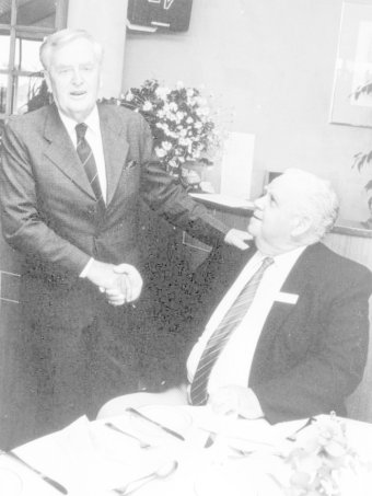 B&W photo of Sir Joh Bjelke-Petersen shakes hands with a seated Russell Hinze on October 11, 1989.