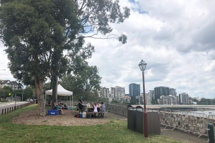 Storm clouds gather as families secure a spot on Brisbane's Kangaroo Point cliffs for NYE fireworks on December 31, 2017.