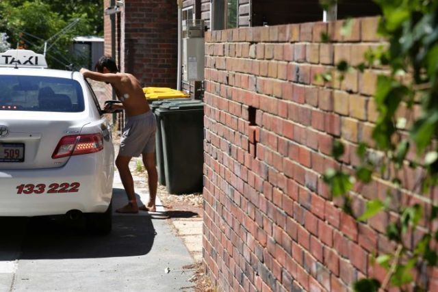 A man wearing a hospital leg band and no shirt leans on a taxi in the driveway of the house.