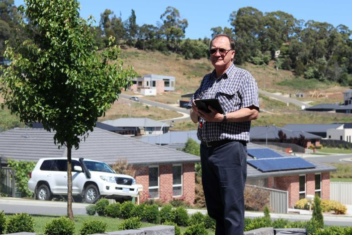Chris Luck stands in front of houses with his tablet computer.