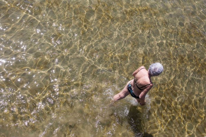 A photo looking down from a pier at a woman walking through water.