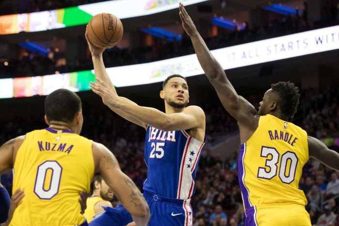 Ben Simmons shoots while being guarded by two LA Lakers players.