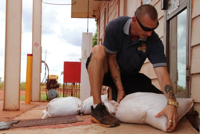 Chef Robert Singleton kneeling down as he sandbags the exterior of Pardoo Roadhouse.