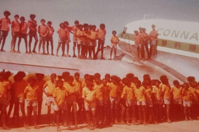 About 50 children standing on aeroplane