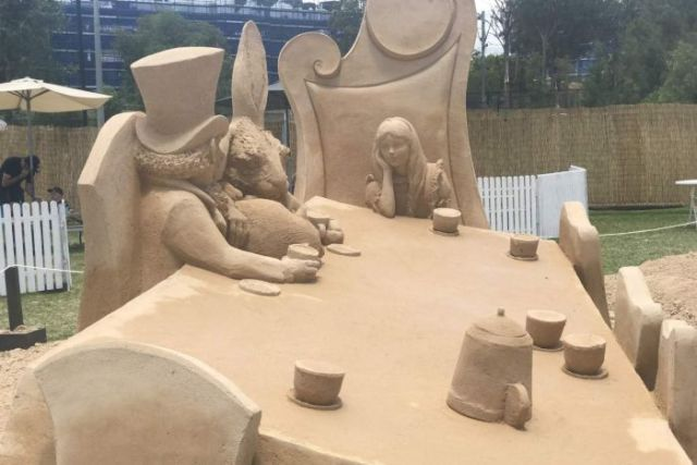 Two people made out of sand talking to each other.