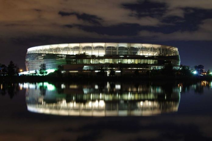 Perth Stadium lit up at night with a reflection in the Swan River.