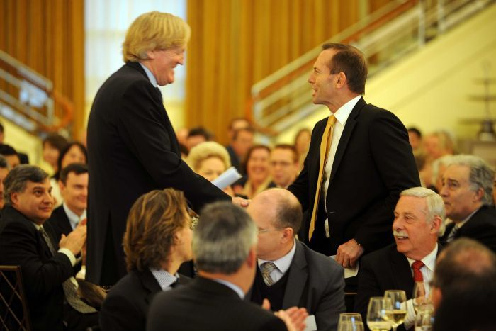 Tony Abbott (right) shakes hands with businessman Ron Walker.