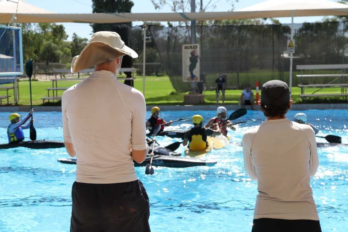 Canoe polo coaches stand by the side of the Alice Springs pool, watching their players train.