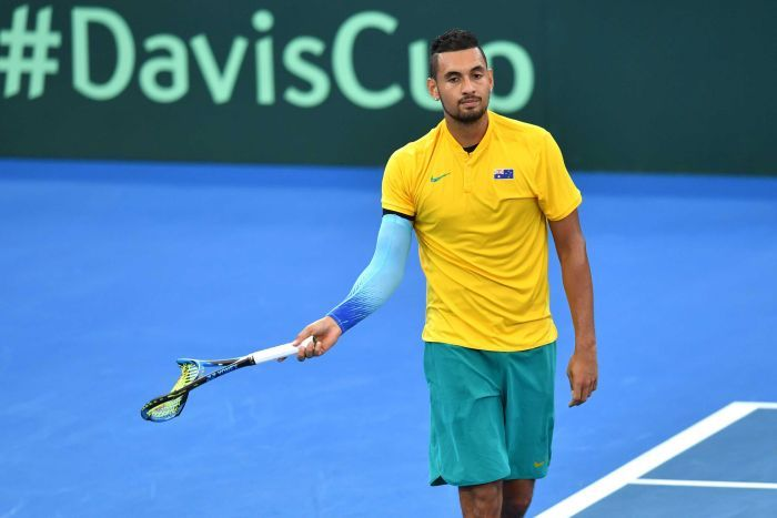 Nick Kyrgios walks off the court with a broken racquet.