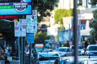 Parking signs in a street packed with cars at West End in inner-city Brisbane.