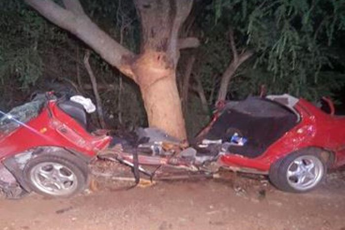 A red car torn almost in half in front of a tree.