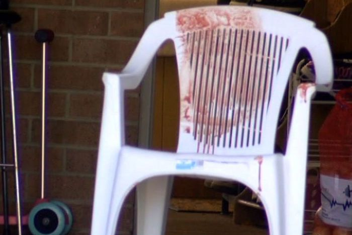 A blood stained plastic garden chair outside a house at Mill Park.