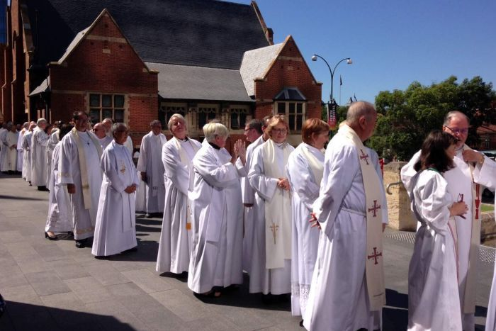 A line of Anglican clergy wearing white vestements outside St George's Cathedrral.
