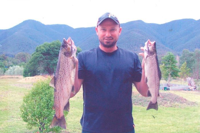 A man shows off two fish he caught.