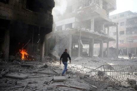 A man walks on rubble at a damaged site after an airstrike in the besieged town of Douma, Syria.